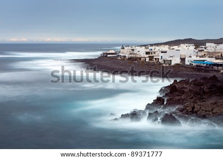 Lanzarote, Canary Islands . The village of El Golfo : white buildings on rocky cliffs in front of the ocean waves .