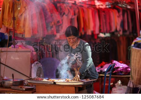 LAOMENG - DECEMBER 16: Food vendor prepares food for sale at a market in Lao Meng, China on December 16, 2012. People from 13 tribes/ethnic groups from China and Laos congregate here to trade daily.