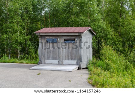 Lapland Finland, toilet on the side of a parking lot on a summer day