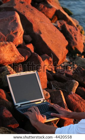 Laptop among rocks with hand