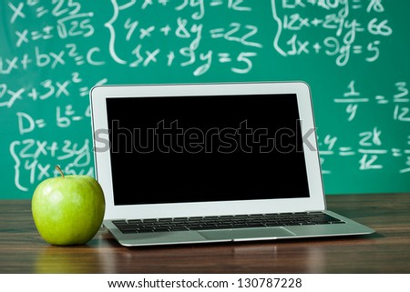 Laptop and apple on the desk in front of blackboard