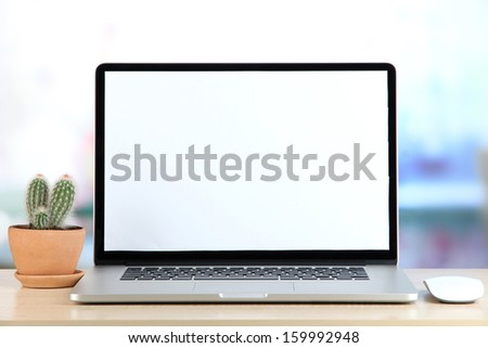 Laptop and cactus in flowerpot on wooden table