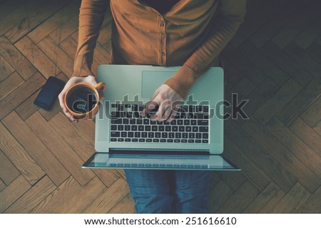 Laptop and coffee cup in girl's hands sitting on a wooden floor #251616610
