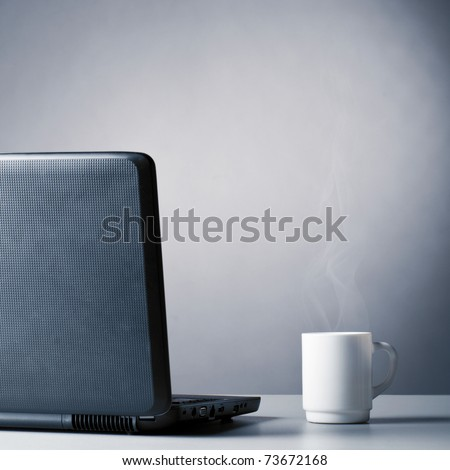 laptop and cup of hot evaporating coffee on table, blue toned