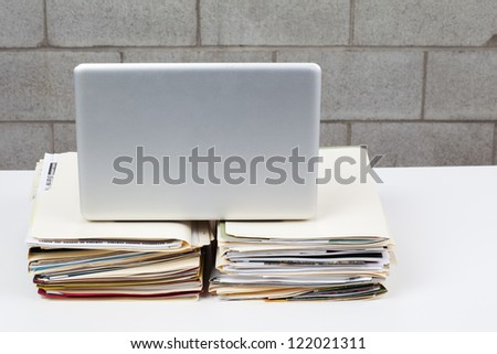 Laptop and folders on desk against brick wall.