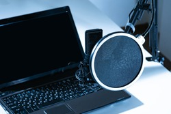 Laptop and microphone close-up. The usual set for voice work. Professional black microphone on a tripod. Black-and-white concept of recording.