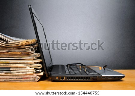 Laptop and newspapers on a table with black background