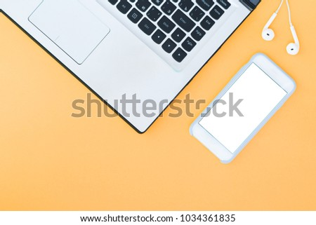 Laptop and smartphone with a white screen and headphones on the orange background. Minimalistic working space with a place for text. Flat Layout Layout. #1034361835