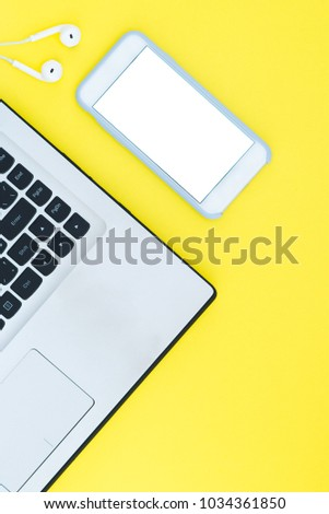 Laptop and smartphone with a white screen and headphones on the orange background. Minimalistic working space with a place for text. Flat Layout Layout #1034361850