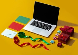 laptop and various Christmas objects for wrapping a gift