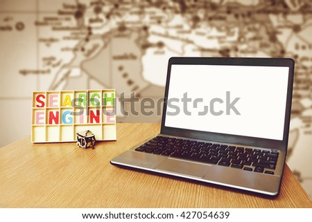 laptop and wooden word search engine with blur part of world map background #427054639