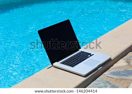laptop at the pool, work on holiday concept