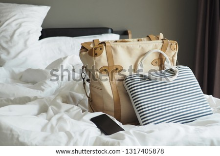 Laptop bag with baggage and smartphone on the unmade bed with blankets and sleep pillows in dark grey bedroom. Lifestyle around travel theme, Healthy sleep habits concept / selective focus, copy space #1317405878