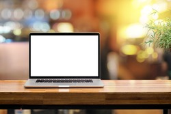 Laptop blank screen on wooden table blurred morning sunshine background