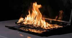 Laptop burning in flames on a desk, fire hazard. losing valuable data, closeup