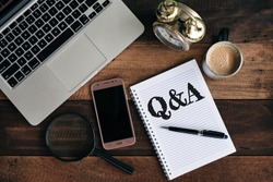laptop, clock, phone, magnifying glass, coffee and notebook with Q&A word. Questions and answer concept