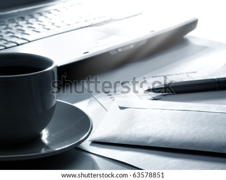 Laptop, coffee, papers and pen
