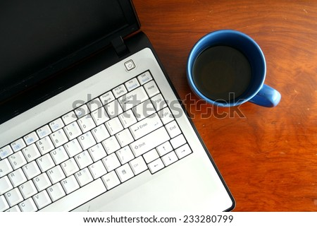 Laptop computer and a blue coffee mug on a table Photo of a Laptop computer and a blue coffee mug on a table