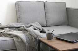 Laptop computer and coffee on desk near grey sofa with blanket. Remote work at home office.