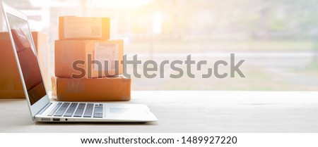 Laptop computer at workplace of start up, small business owner. cardboard parcel box of product for deliver to customer. Online selling, e-commerce, packing concept, Morning light