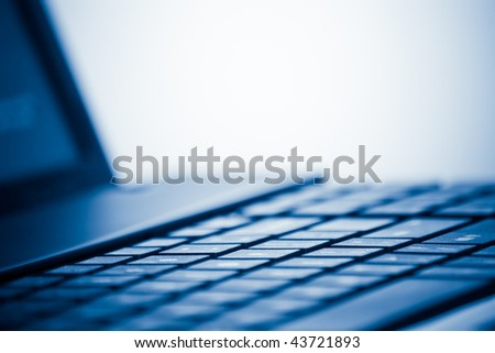 laptop computer detail with lot of copy space and shallow depth of field blue toned
