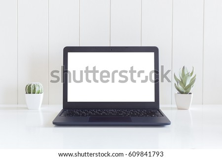 Laptop computer isolated white screen with cactus flowers vase on white wooden desk #609841793