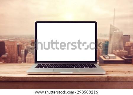 Laptop computer mock up over city skyline. Retro filter effect