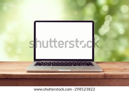 Laptop computer mock up over nature bokeh background. Retro filter effect