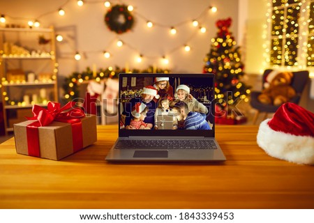 Laptop computer on table with Santa hat and gift box with happy family on screen opening wonderful present. Concept of Christmas and New Year electronic store sales, discounts and giveaways