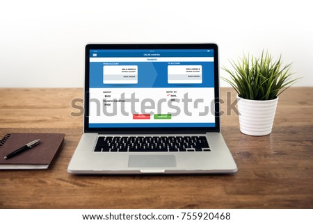 Laptop computer on wood table opening online electronic internet banking transfer page on screen,  financial technology concept