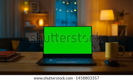 Photo of  Laptop Computer Showing Green Key Screen Stands on a Desk in the Living Room. In the Background Cozy Living Room in the Evening with Warm Lights on.