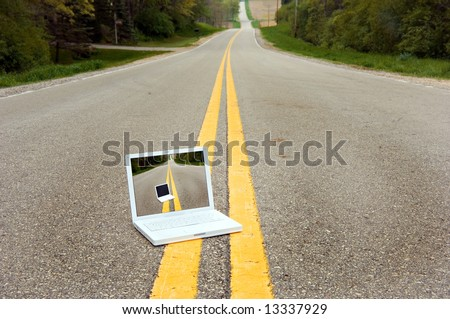 Laptop Computer sitting in the middle of  country road. Concept is working on the road or connecting to your business anywhere.
