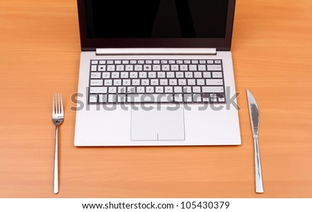 Laptop computer with fork and knife on the table - stock photo