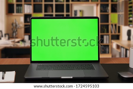 Photo of  Laptop computer with Green screen Mock-up on working desk in office with no people