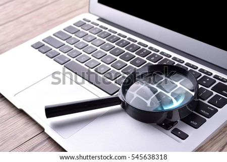 Laptop computer with magnifying glass, concept of search