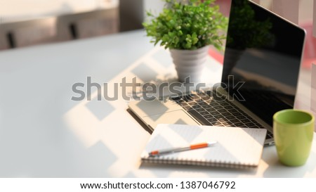 Photo of Laptop computer with notebook, coffee on white table in office workspace.