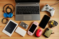 laptop computer with Smartphone and portable game consoles and ebook reader and many electronic gadgets on wooden background.Top view.