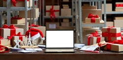 Laptop computer with white blank empty mock up screen on Merry Christmas table with presents gifts boxes in warehouse background. Ecommerce website xmas online shopping and shipping delivery, banner.