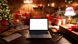 Laptop computer with white blank empty mock up screen on Merry Christmas table with presents gifts, decorated Xmas tree in Santa house background. Ecommerce website online shopping delivery ads.