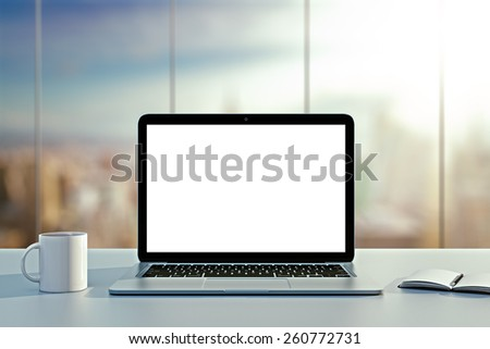 laptop, cup and diary on table in office