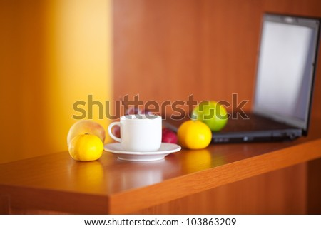 laptop,cup and fruits on the desk