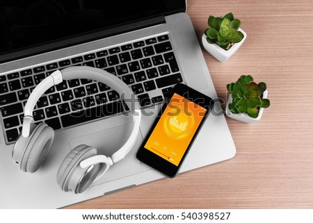 Laptop, headphones and smartphone on a table, close up #540398527