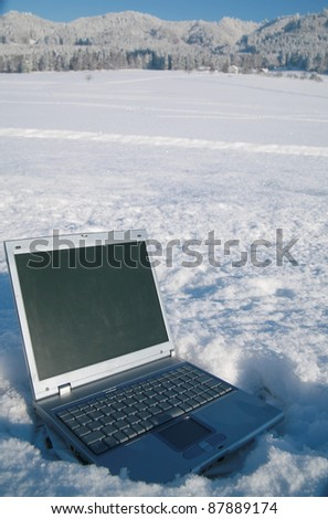 Laptop in a snowy winter landscape scene
