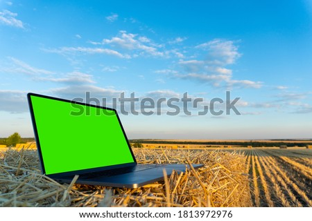 Photo of  Laptop in the autumn field with green chromakey screen