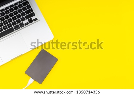 Laptop keyboard, storage drive or hard disk on yellow background with selective focus and crop fragment. Business, backup and copy space concept. #1350714356