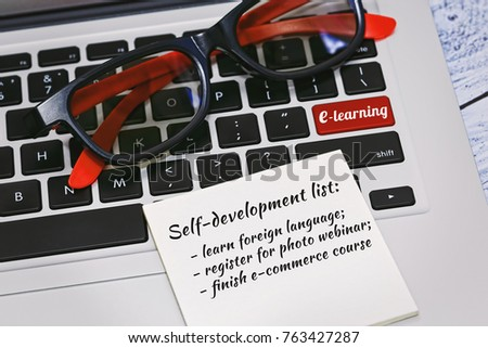 Laptop keyboard with nifty eyeglasses and a to do list on it. Enter key on keyboard replaced with a e-learning concept tagline. To do list is filled up by training courses titles. Selective focus. #763427287