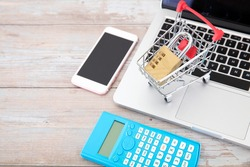 Laptop, mobile phone, calculator and shopping cart model with a lock imply the concept of online shopping security