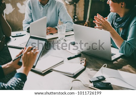 Laptop, mobile phone, tablet and documents on a working table in creative office. Successful teamwork and business startup concept. Toned image