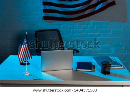 laptop near stationery near american flag in modern office  #1404391583