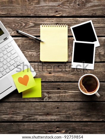 Laptop (notebook) with coffee cup and sticky note paper with notepad on old wooden table.